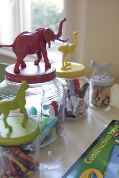 Glass jars with animal lids for kids crafts. Spray paint plastic animals and lids separately, hot glue the two together. Genius!