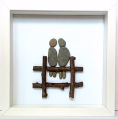 This lovely artwork is the perfect gift to give to someone special or to simply have in your home. Made out of a mixture of pebbles and wood to create two lovers sitting on a fence. Can also be personalized with any wording underneath.Comes in a white or black frame (size 23x23cm) with a white background. *****************************Mae y llun yma wedi cael ei wneud allan o bren a cerrig yr afon i greu dau o bobl ar fens. Mae'n anrheg perffaith i rhoi i ...