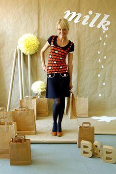 Schönes Kleid aus weicher dunkelblauer Viskose mit unserem Äpfelchenmuster  in blau-rot. Es hat aufgesetzte Taschen mit Knöpfen und einen Kragen.  Tol