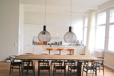 Extra love for this modern, white kitchen and the long table, chairs and wonderful pendants.
