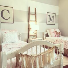 Stripes are a great way to create a feature wall in a bedroom. This shared girls room is perfectly cozy with shabby chic bedding, rustic burlap touches, and a wood ladder to add warmth to the gray striped ️Wall. Custom initial artwork personizes the space Sister Bedroom, Big Girl Bedrooms, Shared Bedrooms, Little Girl Rooms, Shabby Chic Apartment, Shabby Chic Bedrooms, Rustic Girls Bedroom, Apartamento Shabby Chic, Grey Striped Walls