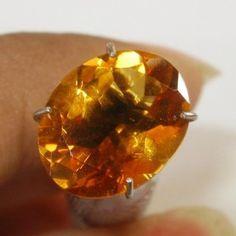 Batu permata Citrine dengan kristal yang sangat bening dan bersih berwarna oranye keemasan, bentuk oval cut, dimensi 10.87mm x 8.62mm x tebal 5.46mm, berat 2.74 carat.