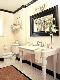 Glossy black crown and base moldings outline this bath with style. The mirror frame and bordered rug add more black, relating to the toile fabric panels visible in the mirror.