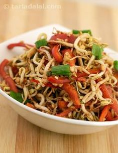 All things 'beany', especially bean sprouts and tofu are very popular in oriental cuisine. Bean sprout salad in a peanut chilli dressing is a tongue-tickling salad of bean sprouts and red capsicum tossed with a tangy and crunchy sauce of garlic, red chillies, soy sauce and peanuts, and garnished with fresh spring onions. Serve the salad as soon as you toss it, to ensure best texture and flavour, and to avoid sogginess.