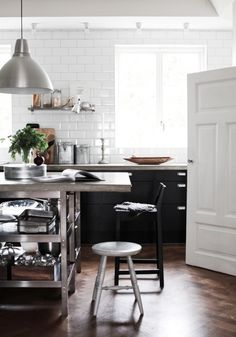 Gorgeous kitchen: white brick walls, stainless steel shelving, black bar stool and silver footstool.