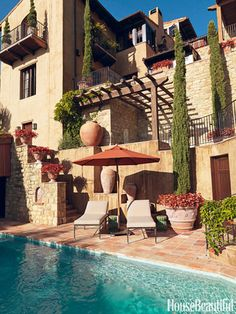 At a Southern California house decorated by Michael S. Smith, the homeowners can stretch out by the pool on Michael Taylor's Montecito Sun Chaises, under an orange Sunbrella umbrella.