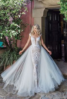 a textural lace sheath wedding dress with a plunging neckline, cap sleeves and a layered tulle skirt