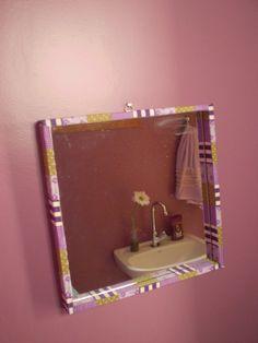 Moldura de espelho revestida de tecido e mais garrafinha no lavabo