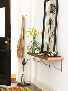 Sometimes an entryway shelf can be more sleek than a cluttered entryway table. Complete the look with framed art and a splash of greenery. #homestaging | bhg.com