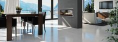 Double-sided Escea DX1000 gas fireplace in a grey statement wall separates dinning and lounge area and also pushes warm air to both living spaces