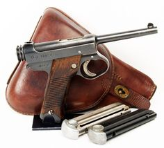 A very early 15.2 date (February 1940) large trigger guard 8mm Japanese Type 14 Nambu pistol made by the Nagoya Arsenal, with two matching transition production serial numbered magazines (one with a nickel tube and the other with a blued tube) in an issue brown leather clamshell holster.