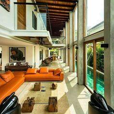 """""""Inspiração Camila Klein do dia"""":  O amplo espaço e as grandes janelas fazem desta residência um local arejado, com vida e contato com a natureza.  O contraste ocorre por conta do sofá e sua cor laranja. Uma decoração incrível em um lugar maravilhoso. #inspiracao #decoracao #arquitetura"""