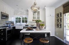 L shaped kitchen features white upper cabinets and black lower cabinets paired with marble countertops and a marble subway tiled backsplash.