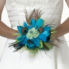 Walk down the aisle in style Peacock Feather Wedding Bouquet. This exquisite peacock feather bouquet is made of vibrant peacock colors and satin trim with a simple gem to complete the look. It is a perfect match for the peacock feather boutonniere. Feather Bouquet, Rose Bridal Bouquet, Bride Bouquets, Bouquet Wedding, Bridesmaid Bouquets, Floral Bouquets, Shell Bouquet, Feather Boutonniere, Bridesmaid Ideas