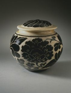Lidded Jar (Guan) with Floral Scrolls China, probably Henan Province, late Jin dynasty or early Yuan dynasty, about 1200-1300 Furnishings; Serviceware Cizhou ware type, wheel-thrown stoneware with cream glaze and wax-resist and carved black overglaze decoration Height: 4 7/8 in. (12.4 cm); Diameter: 5 in. (12.7 cm) @LACMA