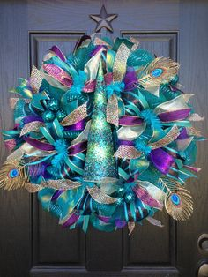 Wreath by Glitzy Wreaths This gorgeous Peacock Christmas mesh wreath is made with turquoise/teal mesh and purple deco ribbon from http://www.trendytree.com. It is accented with a beautiful beaded Christmas tree  and gold feathers. #trendytree #christmas wreath