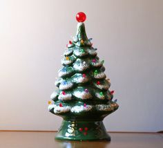 Vintage lighted green ceramic Christmas tree.    Large vintage 1970s green ceramic Christmas tree with multi-colored plastic ornaments. molded base, central lighting cord with switch, light texture snow on tip of the branches. Really beautiful when lit up!