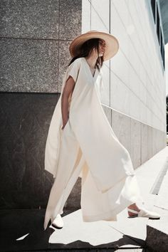 all white caftan over wide leg trousers