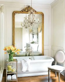 A beautiful master bathroom with a massive antique mirror behind a clean freestanding bathtub and a chandelier above,  a minimalist glass and Calacatta marble shower juxtaposed by traditional moldings, lovely marble countertop and vanity featuring a paneled mirrored wall and mirrored sconces,  and finally a luxe velvet vanity seat adds a touch of green.