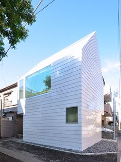 Townhouse in Takaban by Niji Architects features a steeply pitched roof, windowless gables and strips of horizontal steel cladding