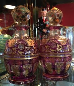 "Moser type aperitif or cologne bottles. Purple-cut-to-clear crystal with intaglio and hand painted gold decorations. Late 19th C, Bohemia. @7.5"" tall"