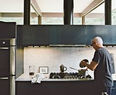 The couple made the most dramatic changes in the kitchen. They installed Carrara marble and custom oiled-steel cabinetry. The artwork is by Cecil Touchon. Near the Wind Crest cooktop is a Bosch oven.