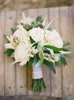 The bridesmaids will carry clutch bouquets of white hydrangea, white lisianthus, white astilbe and bay laurel; wrapped in navy ribbon with the stems showing.
