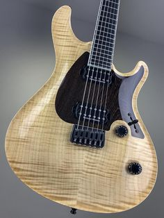 Mayones Regius CoreGuard 6 Master Builder Collection 2018   Flamed Maple top   Pickguard shaped Wenge intarsia   Trans Natural Gloss top finish   Natural wood body top binding   Mahogany Khaya body wings   11-ply neck-thru-body section   Trans Natural Matt back finish   Ebony fingerboard   Luminlay SGM-23 Super Green in Black pipe side dot markers   24 Ferd Wagner jumbo frets   3-ply White ABS / Gray Acrylic Pearl binding