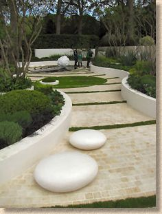 Simplistic large landscape. Raised curved garden bends leading to a focal point, divided by grass strips and large pebbles.