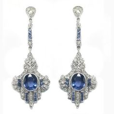 This is a wonderful pair of 18k white gold earrings inspired from the Art Deco period . These beautiful dangling earrings are centered with wonderful oval cut sapphires that weigh approximately 2.50ct. The earrings are also adorned by approximately 1.10ct of sparkling round cut diamonds. The color of these diamonds is H with VS clarity. These earrings has beautiful open work, milgrain and gallery designs