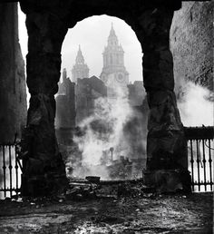 The spires of St. Paul's Cathedral as seen through the archway of a smoldering ruin after a Nazi incendiary bomb attack during the Blitz. Photograph by Hans Wild. London, December 1940.