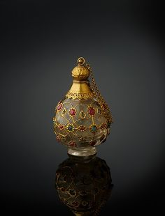 Object Name: Bottle Date: 1650–1700 Geography: North India Medium: Rock crystal, inlaid with gold wire, rubies, and emeralds, with gold collar, stopper, and foot