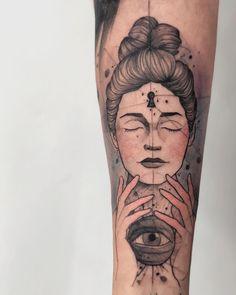 Tatuagem criada por Felipe Mello do Rio de Janeiro. Rosto feminino colorido no braço com olho que tudo vê.