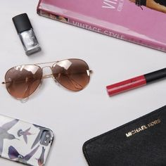 "The essential kit for cool spring days - exurbe cosmetics wrecking ball, ""suck my kiss"" lipgloss in fiery hot ""pink temptation"", a good read (here vintage styles), your shades, purse and phone. Off you go for a laid back afternoon at a cozy café. #style #exurbecosmetics #nailvarnish #nailpolish #lipgloss"