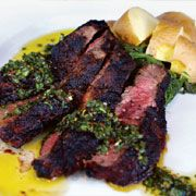 Grilled flatiron steak with roasted potatoes, sautéed spinach and chimichurri sauce