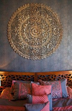 Asian inspired home interior design idea. Wood head board and carved wood circle wall deco