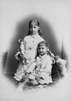 Princesa Marie de Hesse (à direita) sentada, a perna esquerda dobrada sob sua direita; ela olha para frente. Princesa Alix de Hesse está à direita de Marie, seu braço esquerdo em volta dos ombros de Marie, uma boneca em sua mão direita. Elas usam vestidos idênticos. Julho de 1878.