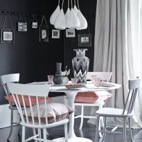 Revamps chairs with a coat of white or grey paint and contrast against a black wall. Photography: Mark Scott. Find more dining room ideas at housebeautiful.co.uk