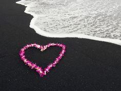 pink heart on black sand