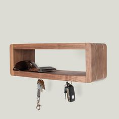 A walnut shelf ideally designed for your front entrance. Empty your pocket contents and hang your keys on one of the five magnets and youll always know where everything is on your way out. This walnut shelf with maple splines is designed to float on the wall with no visible hardware. Requires two screw holes in the wall. Finished with Osmo Top Oil to retain its natural matte finish. - solid walnut wood - maple splines for added strength - 5 evenly spaced magnets secured flush to the bottom…