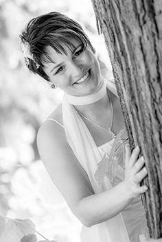 Glückliche Braut hinter dem Baum