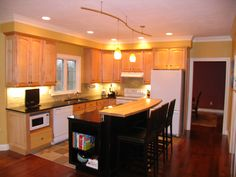 """Updates to an existing """"U-shaped"""" kitchen.  We removed the ell, and added an island to help circulation.  New: black island, granite counter and maple breakfast bar, subway tile backsplash, slate floor, paint and lighting."""