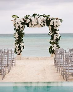 A huppa of monstera leaves and white phalaenopsis orchids was built on the edge of the beach. The simple structure framed the couple and the sea.