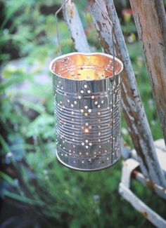 Tin Can Lanterns hung from branches for extra sparkle #designsponge #dssummerparty