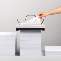 Stack by Mugi Yamamoto - The compact Stack printer by industrial designer Mugi Yamamoto is simply placed on top of a pile of A4 paper, rather than loading paper into the device in batches. The sheets are fed through rollers underneath the machine and exit on the top. | Dezeen