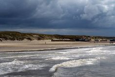 The sea and beach at Julianadorp 2015. It was a cloudy/rainy day. In the background you see the dark clouds hanging over the beach. In the foreground you can see the waves, which are enlighted by the sun