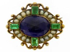 Rare amethyst, emerald and pearl brooch by Carlo Giuliano, English, circa 1890. A yellow gold brooch set with one central oval faceted amethyst in a collet setting, encircled by a single row of pearls in bead settings, and set at the cardinal points with four emerald-cut emeralds in collet settings, further ornamented with scrolled decoration flanking the emeralds, the reverse with a hinged pin and scroll clasp, and marked 'C.G.' in a circle.