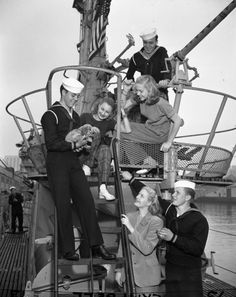 Sailors aboard the U.S.S. Catfish, photographed by Bob Campbell on Feb 22, 1947. If youre looking to pick up a girl two years after World War II, you could do worse than, Im a sailor on a submarine, would you like to hold my puppy? Theres a larger version of this photo in the post.