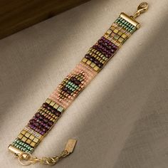 One of my handwoven, loomed bracelets. Seed beads, Czech glass beads, crystal. Lime, pink, and ruby are major colors. 14K gold-fill clasp.