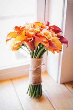fall wedding center pieces | orange and yellow wedding bouquet wrapped with burlap
